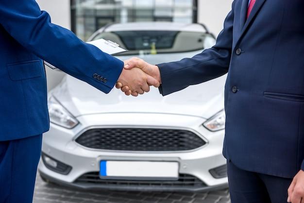 Apretones de manos de dos hombres contra el capó de un coche