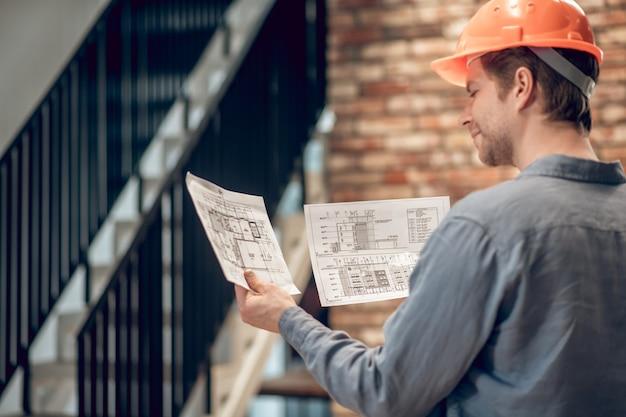 Aprobación. vista posterior del hombre feliz en casco protector mirando planes de construcción y sosteniendo en sus manos de pie frente a las escaleras