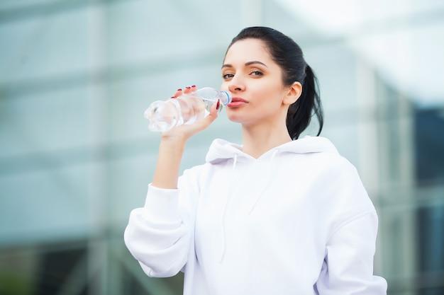 Aptitud. hermosa mujer agua potable y escuchar música después de correr