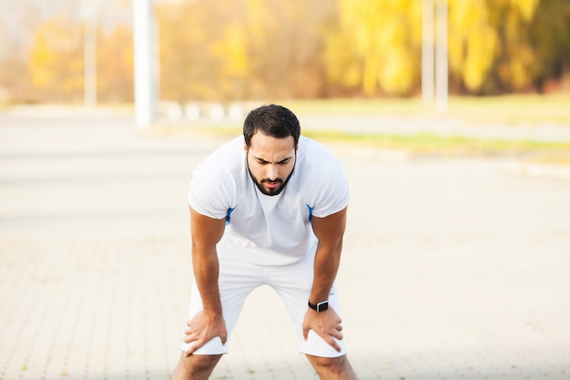 Aptitud. hombre cansado corredor descansa después de correr en la calle de la ciudad