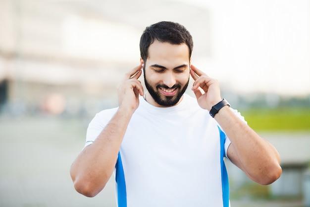 Aptitud. hombre deportivo con auriculares para escuchar música en la mañana en el parque
