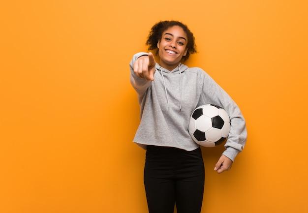 Aptitud joven mujer negra alegre y sonriente. sosteniendo un balón de fútbol.