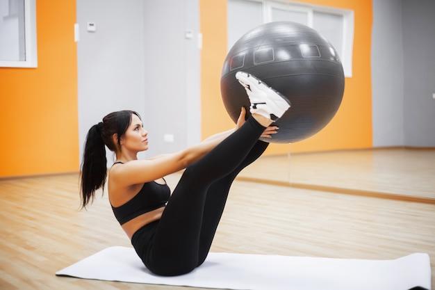 Aptitud. mujer joven entrenando con fitness ball
