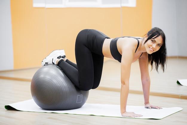 Aptitud. mujer joven fitness con fitball gris. entrenamiento crossfit