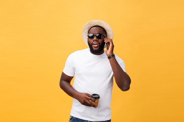 Apuesto afroamericano con teléfono móvil y taza de café para llevar.