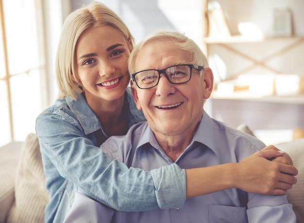 Apuesto anciano y hermosa joven están abrazando.