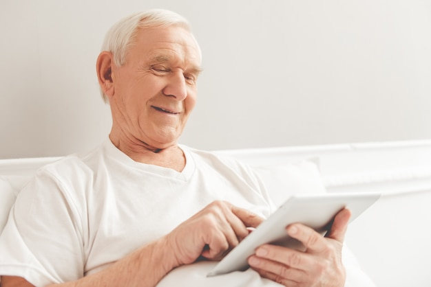 Apuesto anciano está usando una tableta digital y sonriendo