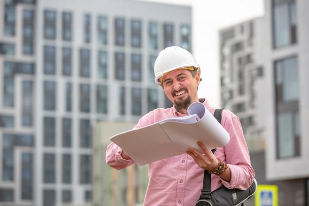 Apuesto arquitecto o supervisor de pie al aire libre en un sitio de construcción sosteniendo un plano en sus manos