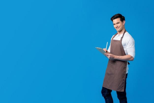 Apuesto barista con orden de escritura de delantal en el portapapeles