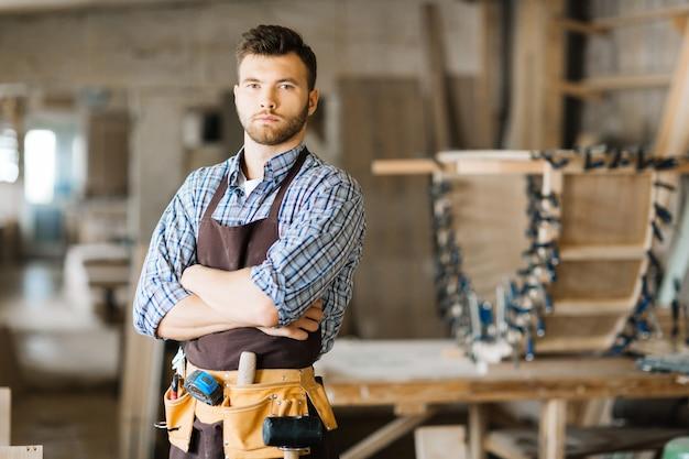 Apuesto carpintero posando para fotografía
