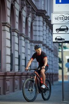 Apuesto ciclista montando en bicicleta, pensando en el éxito futuro, ganar en concursos, nuevos logros deportivos. grandes expectativas. deportista tomando un descanso después de la carrera