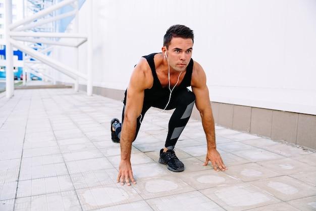 Apuesto deportista muscular en auriculares en posición de partida, preparándose para correr