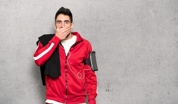 Apuesto deportista que cubre la boca con las manos por decir algo inapropiado sobre una pared texturizada