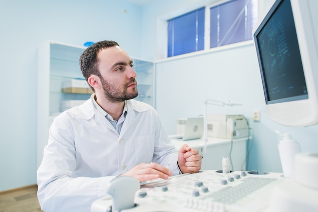 Apuesto doctor usando una máquina de ultrasonido