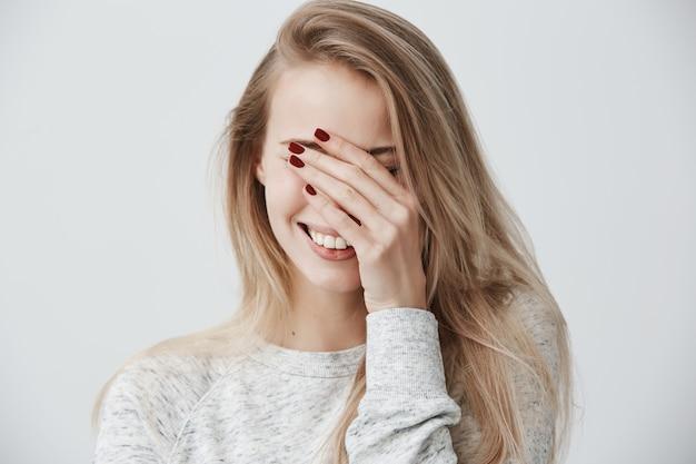 Apuesto emocional joven mujer caucásica con cabello largo y rubio, cerrando los ojos con la mano mientras se ríe a carcajadas, feliz con buenas noticias positivas, sonriendo ampliamente, mostrando dientes blancos y rectos