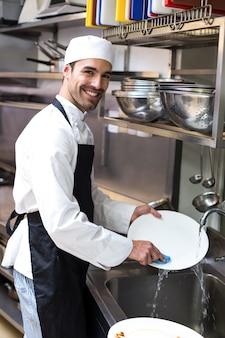 Apuesto empleado lavando platos