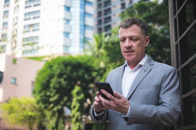 Apuesto empresario gerente ejecutivo en traje con teléfono móvil inteligente táctil para trabajar en el ciberespacio, confiado y exitoso con mensaje de teléfono celular en línea, caminando en la ciudad