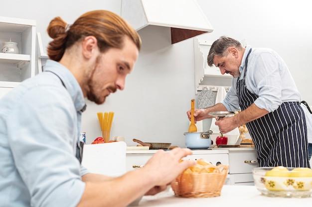 Apuesto hijo y padre cocinando