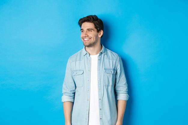 Apuesto hombre adulto sonriente en traje casual, sonriendo y mirando a la izquierda en oferta promocional, de pie contra el fondo azul.