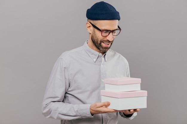 Apuesto hombre sin afeitar con brislte sostiene dos cajas, feliz de recibir el regalo de un amigo en el cumpleaños