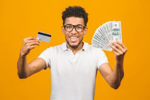 Apuesto hombre afroamericano barbudo en casual celebración pila de dinero y una tarjeta de crédito