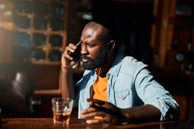 Apuesto hombre afroamericano con cigarro hablando por teléfono celular