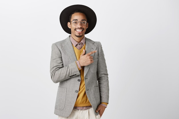 Apuesto hombre afroamericano elegante apuntando con el dedo a la derecha en el banner promocional