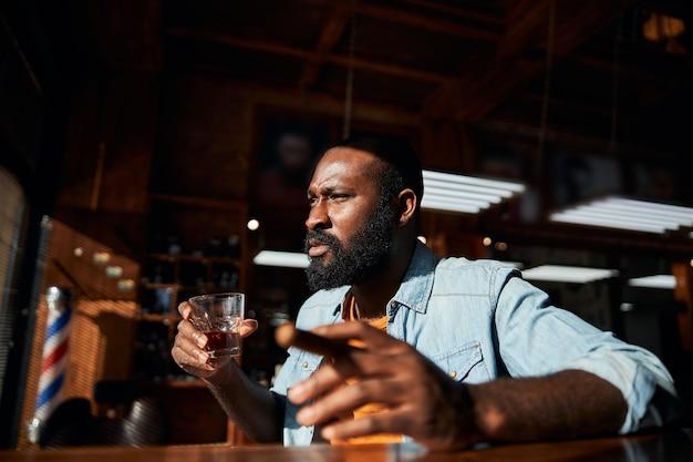 Apuesto hombre afroamericano fumando puros y bebiendo whisky