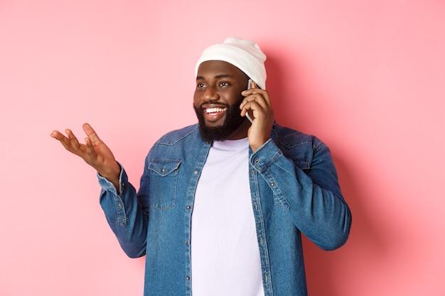 Apuesto hombre afroamericano moderno hablando por teléfono móvil, sonriendo y discutiendo algo, de pie sobre fondo rosa