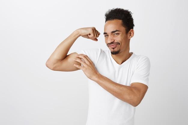 Apuesto hombre afroamericano seguro y fuerte flexionando bíceps, entrenamiento en el gimnasio, mirando descarado