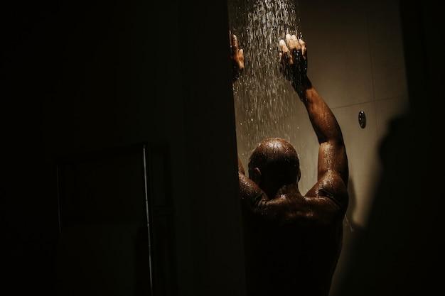 Apuesto hombre afroamericano con torso desnudo toma ducha