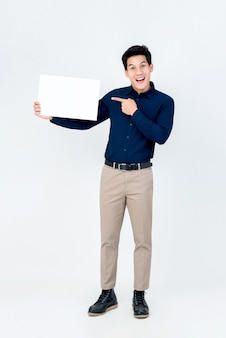 Apuesto hombre asiático sonriente poiting mano al papel en blanco