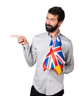 Apuesto hombre con barba sosteniendo muchas banderas y apuntando a la lateral