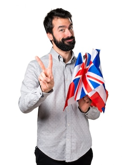 Apuesto hombre con barba sosteniendo muchas banderas y contando dos