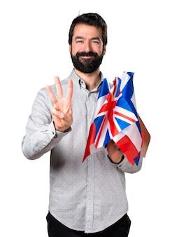 Apuesto hombre con barba sosteniendo muchas banderas y contando tres