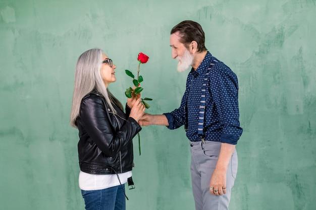 Apuesto hombre barbudo anciano dando hermosa rosa fresca roja a su encantadora esposa sonriente con el pelo largo y liso gris, de pie sobre el fondo verde de la pared