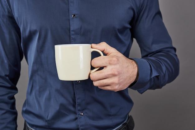 Apuesto hombre barbudo con elegante barba de pelo y bigote en la cara seria en camisa con taza blanca o taza bebiendo té o café en estudio en gris