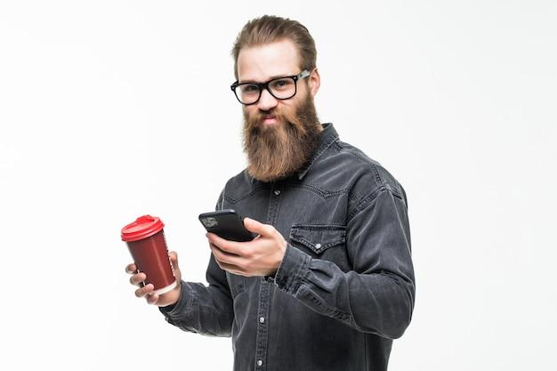 Apuesto hombre barbudo con elegante barba de pelo y bigote utilice el teléfono móvil con taza o taza bebiendo té o café en el espacio blanco