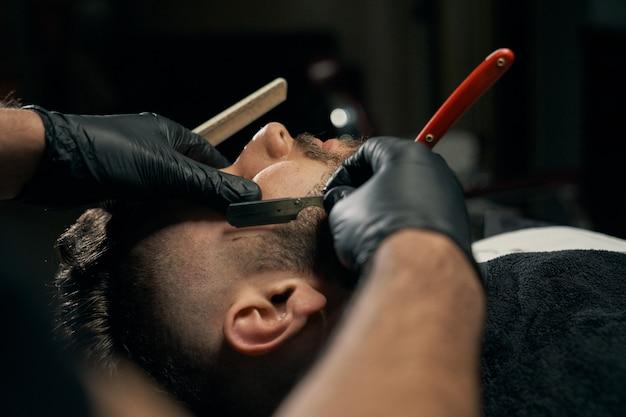 Apuesto hombre barbudo es afeitado por peluquero