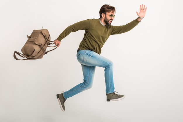 Apuesto hombre barbudo con estilo saltando corriendo aislado vestido con sudadera con bolsa de viaje, jeans y gafas de sol, viajero loco de prisa