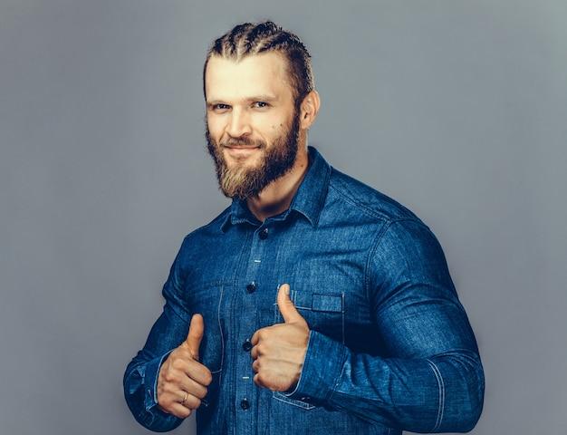 Apuesto hombre barbudo en ropa casual está apuntando lejos, mirando a cámara y sonriendo