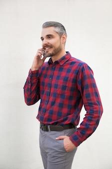 Apuesto hombre barbudo sonriente hablando por teléfono inteligente