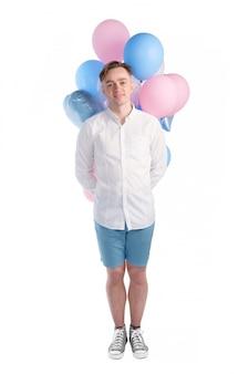 Apuesto hombre caucásico en camisa blanca riendo y sosteniendo globos rosados y azules detrás aislado detrás