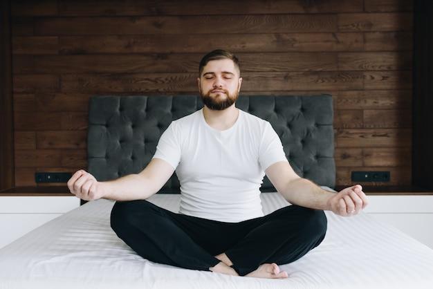 Apuesto hombre caucásico meditando y teniendo en cuenta su cama en el dormitorio