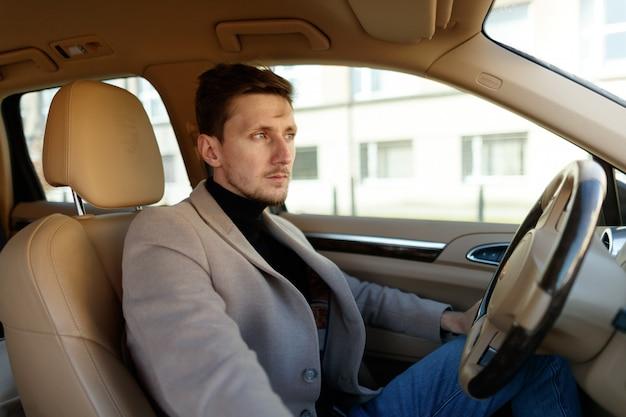 Apuesto hombre caucásico está mirando a través del parabrisas en el nuevo salón del automóvil beige
