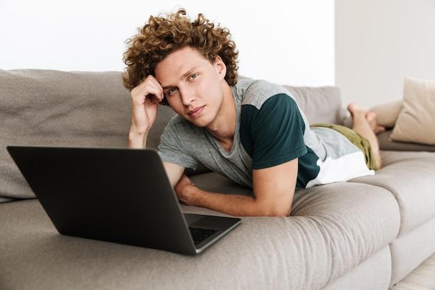 Apuesto hombre concentrado se encuentra en el sofá usando laptop