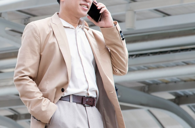 Apuesto hombre de negocios mediante teléfono móvil o teléfono inteligente en la ciudad moderna.
