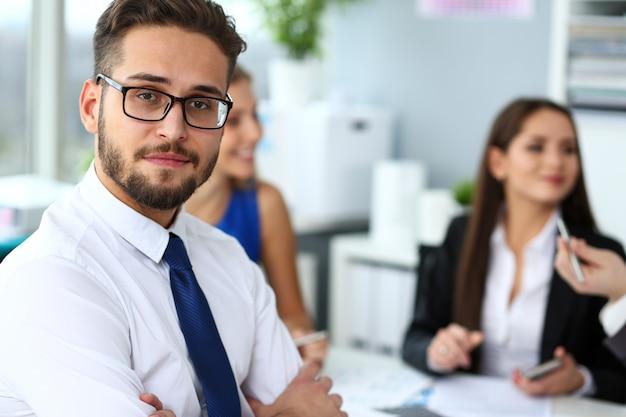 Apuesto hombre de empleado barbudo sonriente con gafas