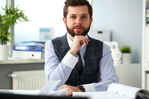 Apuesto hombre de empleado barbudo sonriente en el lugar de trabajo de oficina