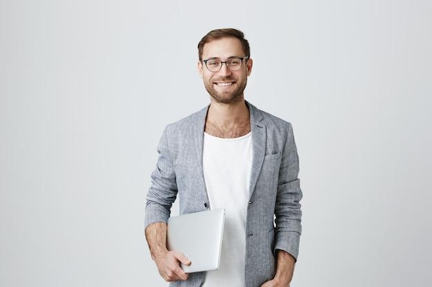 Apuesto hombre emprendedor elegante en vasos con laptop